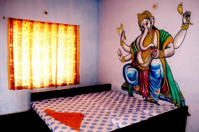 Painted deity towering toward two cots together in a hotel. Took it in 2011, Varkala Beach (Kerala, India).